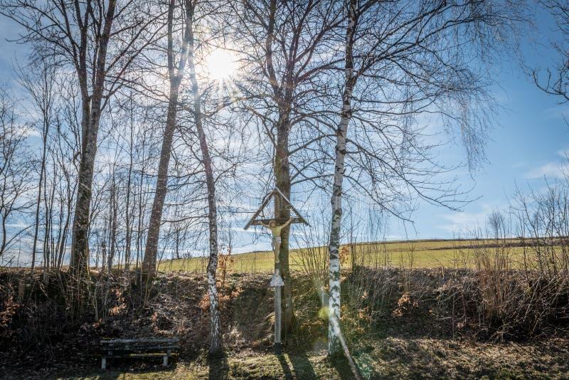 Croix de manière à un sentier de randonnée en Bavière avec le banc en bois et le soleil, Allemagne image stock