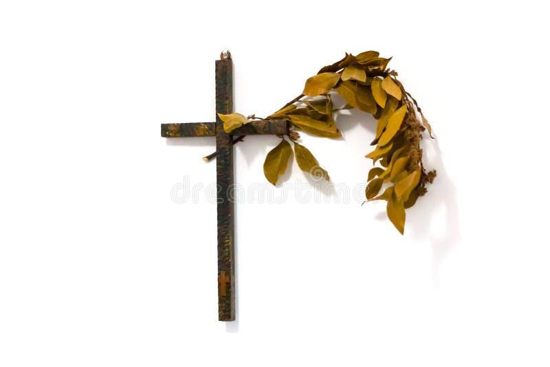 Croix en bois avec une branche de laurier sur le mur blanc photo stock