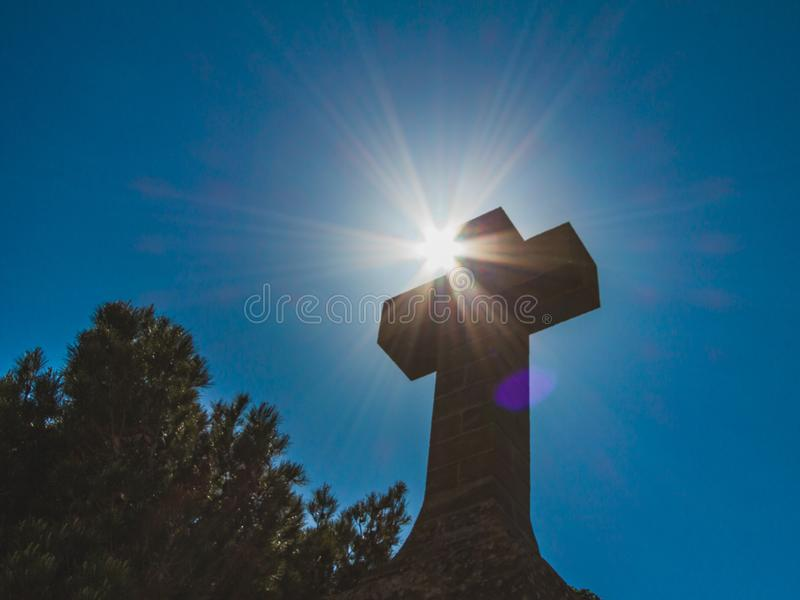 Croix en pierre chrétienne sur le fond bleu-foncé de ciel contre le soleil r images libres de droits