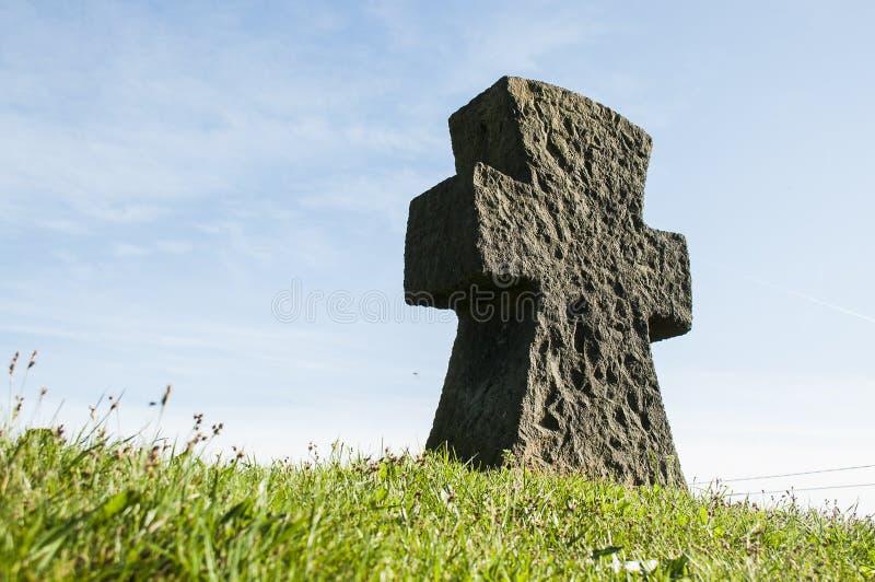 Croix en pierre sur l'herbe avec un ciel bleu photo libre de droits
