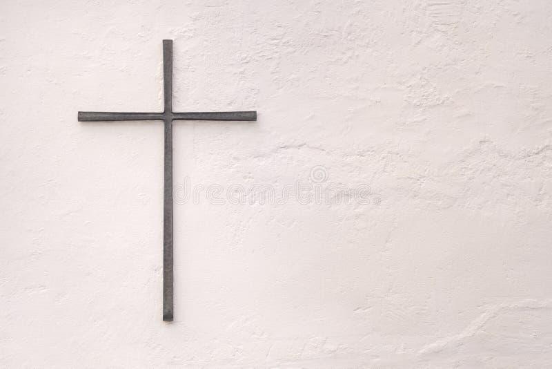 Croix faite de métal sur un mur blanc photographie stock libre de droits