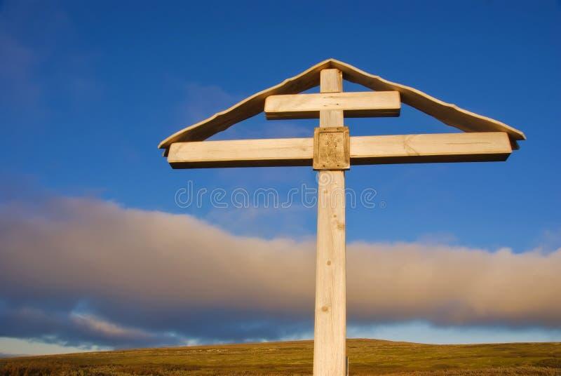 Croix orthodoxe au coucher du soleil au-dessus de l'océan arctique photographie stock