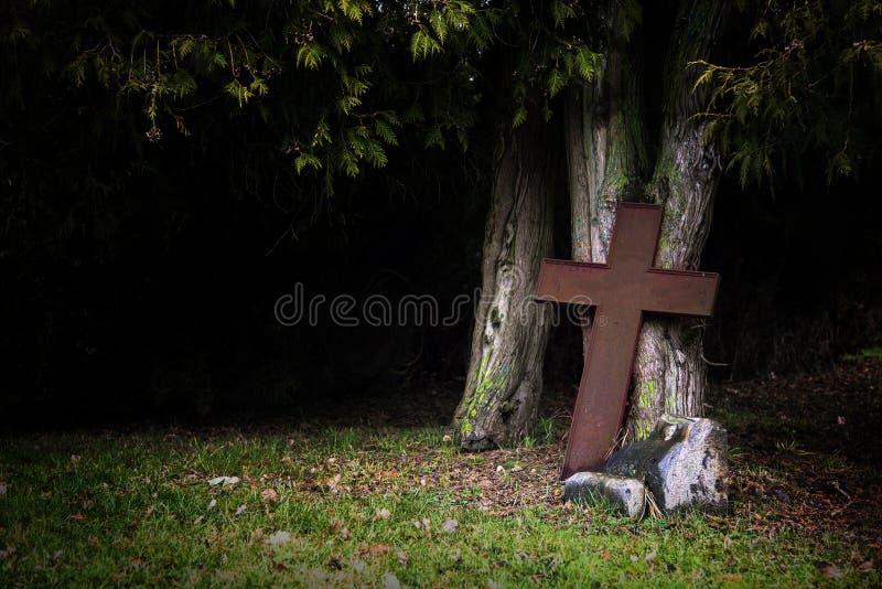 Croix rouillée faite de métal se penchant contre de vieux troncs d'arbre dans le sha image libre de droits