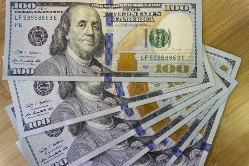 Crolled-Stapel von 100 neuen Dollarscheinen auf hölzernem Hintergrund stockfoto