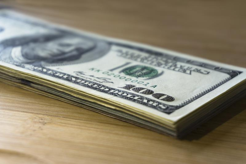 Crolled-Stapel von 100 neuen Dollarscheinen auf h?lzernem Hintergrund lizenzfreie stockbilder