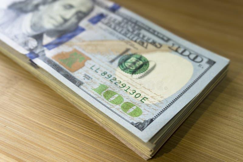 Crolled-Stapel von 100 neuen Dollarscheinen auf h?lzernem Hintergrund lizenzfreie stockfotografie