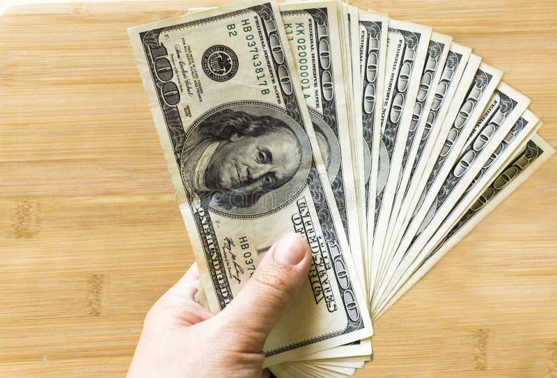 Crolled-Stapel von 100 neuen Dollarscheinen auf h?lzernem Hintergrund stockfoto