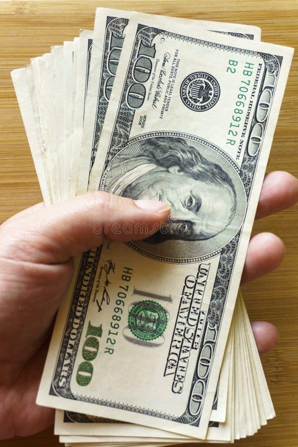 Crolled-Stapel von 100 neuen Dollarscheinen auf h?lzernem Hintergrund lizenzfreies stockbild
