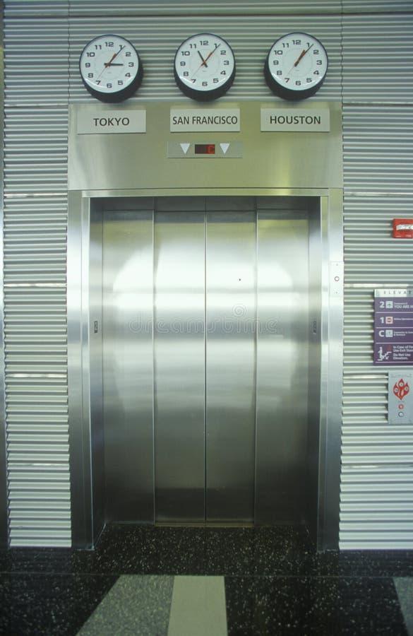 Crome portas do elevador & fusos horários do mundo, aeroporto internacional de Cleveland imagem de stock royalty free