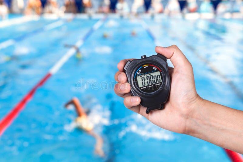 Cronómetro que se sostiene a mano con las competencias de la natación imagen de archivo