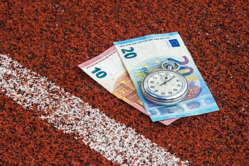 Cronômetro e dinheiro velhos do esporte na borracha da pista de atletismo foto de stock