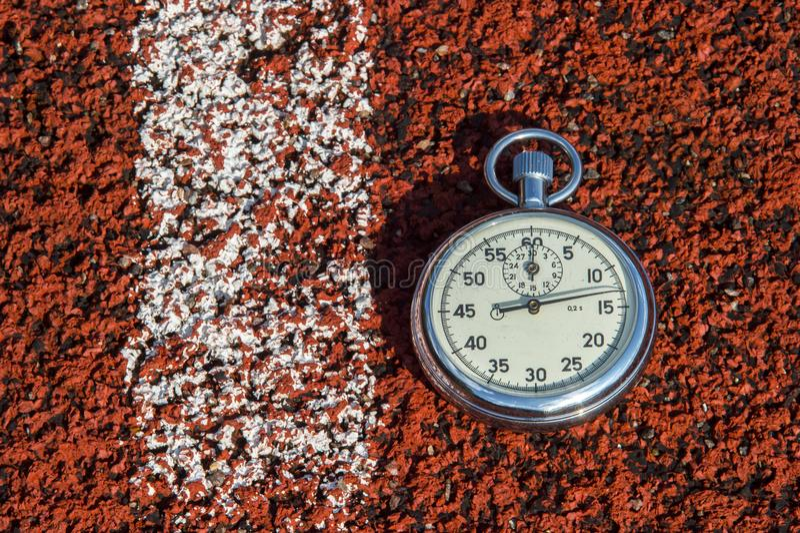 Cronômetro velho do esporte na borracha da pista de atletismo fotografia de stock