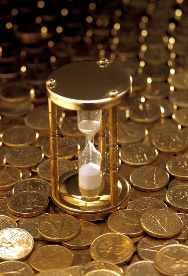 Cronômetro empilhado sobre de moedas de ouro imagens de stock royalty free
