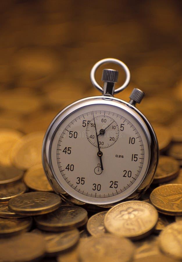 Cronômetro empilhado sobre de moedas de ouro foto de stock