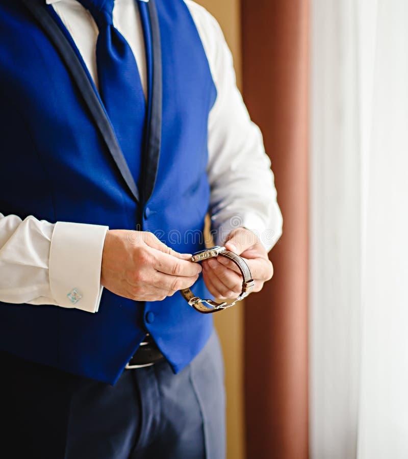 Cronometre o mantimento para a nomeação importante, olhares de um homem em seu relógio da reunião séria fotos de stock royalty free