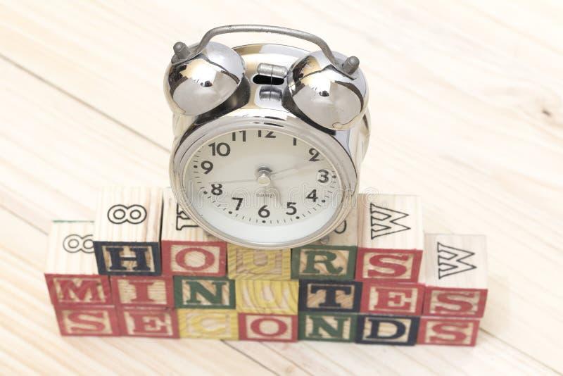 Cronometri con i cubi di legno sulle ore di legno di parole della tavola, i minuti, secondi si raffreddano fotografie stock libere da diritti