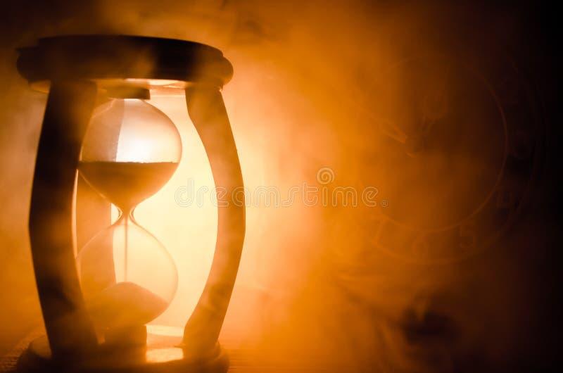 Cronometri il concetto La siluetta dell'orologio della clessidra ed il fumo su fondo scuro con il freddo blu rosso giallo arancio fotografia stock libera da diritti