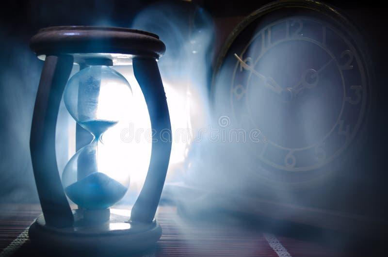 Cronometri il concetto Siluetta dell'orologio della clessidra e di vecchio orologio di legno d'annata con la freccia e fumo su fo fotografie stock