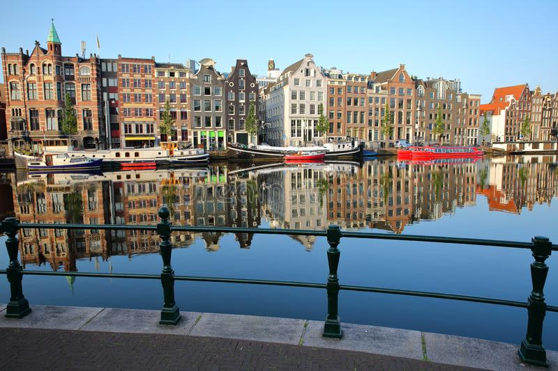 Crooked and colorful heritage buildings and houseboats, overlooking Amstel river with perfect reflections, Amsterdam. Netherlands royalty free stock photos