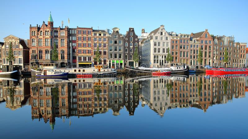 Crooked and colorful heritage buildings and houseboats, overlooking Amstel river with perfect reflections, Amsterdam. Netherlands stock image