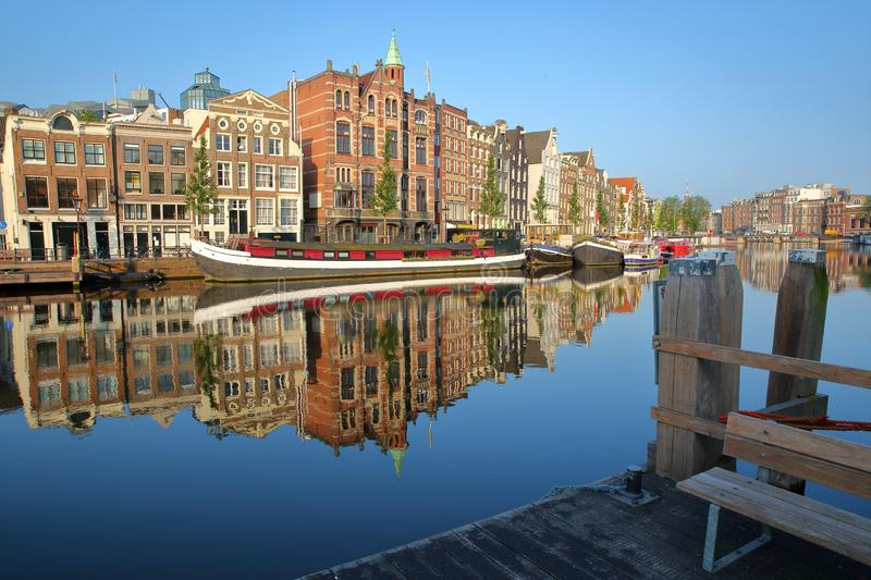 Crooked and colorful heritage buildings and houseboats, overlooking Amstel river with perfect reflections, Amsterdam. Netherlands stock photography