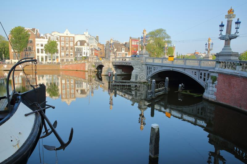 Crooked and colorful heritage buildings and houseboats, overlooking Amstel river with perfect reflections, with Blauwbrug bridge. Amsterdam, Netherlands royalty free stock image