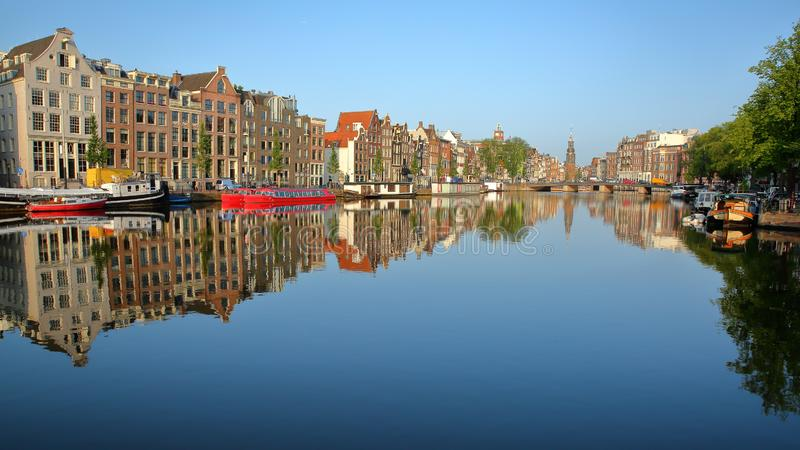Crooked and colorful heritage buildings and houseboats, overlooking Amstel river with perfect reflections. With Munttoren historic tower with a carillon in the royalty free stock photo