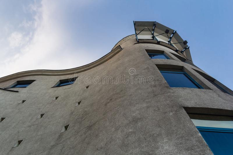 A crooked concrete building with blue windows. stock image
