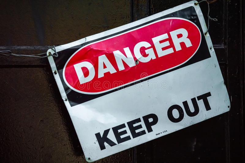 Crooked old metal warning sign that reads DANGER KEEP OUT. Copy space. Graphic resource stock photography