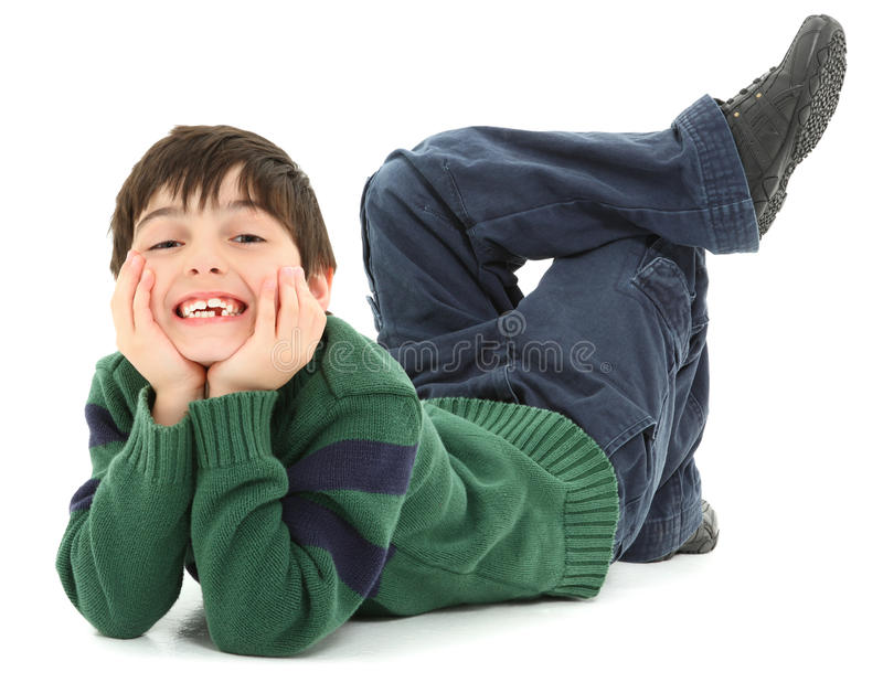 Crooked Twisted Child Smiling. Adorable and very flexible 7 year old french american boy laying on belly with legs twisted behind him. Smiling royalty free stock image