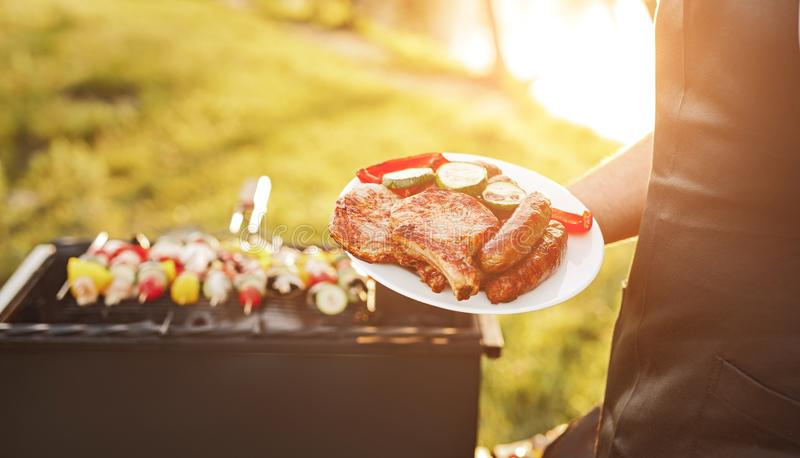 Crop chef with roasted meat and vegetables near grill. Unrecognizable male in apron holding plate with delicious fried steaks and vegetables standing near grill royalty free stock photo