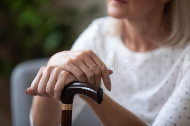 Close up of upset elderly woman use walking cane stock photos