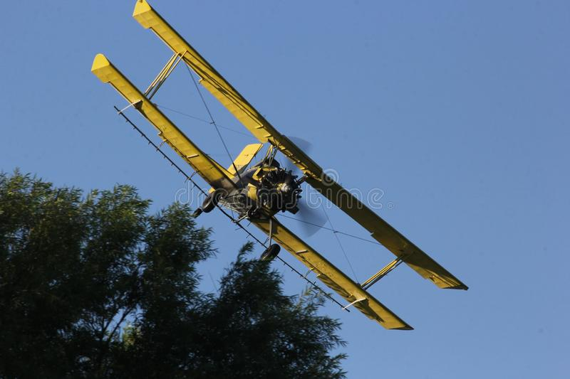 Crop Duster flying over the Iowa farm fields. royalty free stock photos