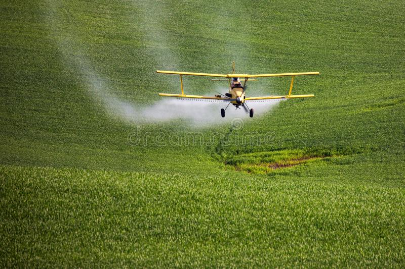 Crop Duster spraying a farm field. stock photos