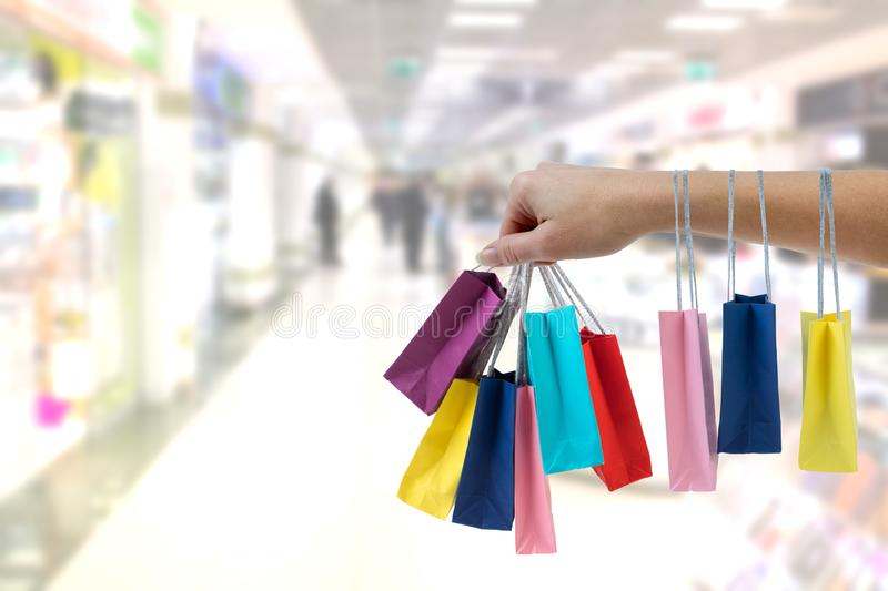Crop female hand holding colorful paper bags on background of shopping center. stock images