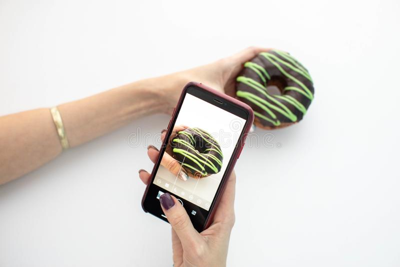 Woman photographing donut with smartphone stock image