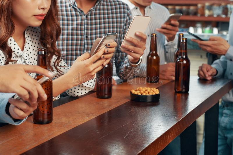 Crop friends in bar absorbed with gadgets royalty free stock image