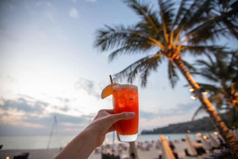 Crop hand with beverage on beach royalty free stock images