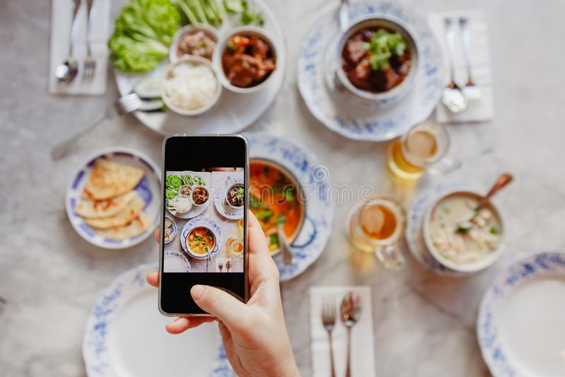 Crop hand taking pictures of food on table royalty free stock images