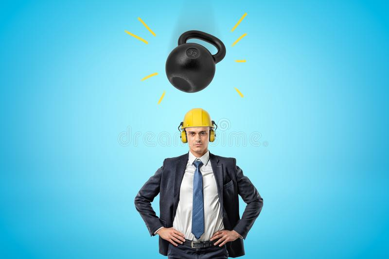 Crop image of businessman in yellow hard hat with ear defenders, standing with hands on hips, and big heavy kettlebell. Falling down onto his head. Construction stock image