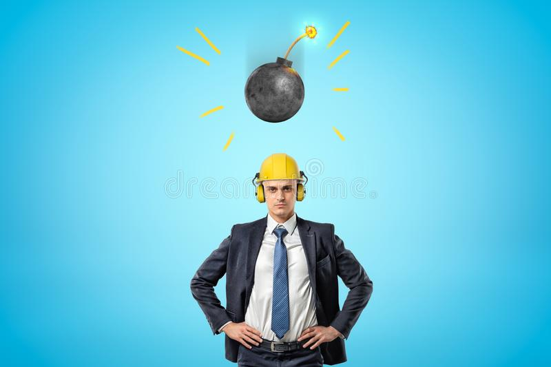 Crop image of businessman in yellow hard hat with ear defenders, standing with hands on hips, and round bomb falling. Down on him. Be prepared. Be ready for stock photography