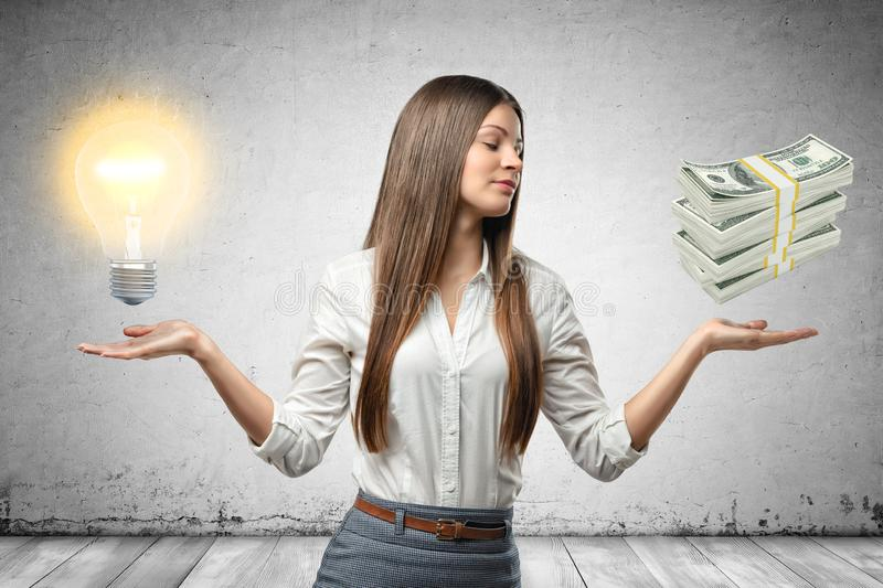Crop image of young beautiful businesswoman, hands at sides, palms facing up and levitating lightbulb and stack of cash. Generate ideas. Develop business. Make royalty free stock photography
