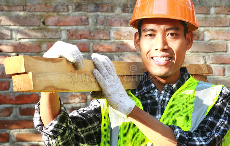 Crop images of man worker carrying wood smiling royalty free stock image