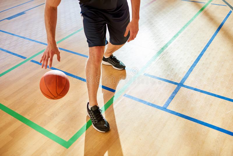 Crop man dribbling basketball ball. Crop basketball player dribbling ball on court floor during match royalty free stock images