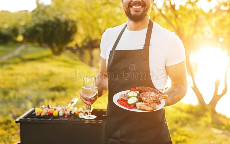 Crop man with meat and wine on lake shore. Anonymous chef with glass of wine and plate of grilled chicken and sausages with vegetables smiling while standing on royalty free stock image