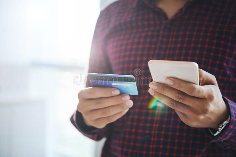 Crop man using smartphone with credit card royalty free stock images