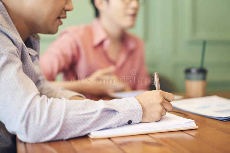 Crop man writing in notepad. Crop side view of men writing in notepad while sitting with coworker at table on coffee break stock image