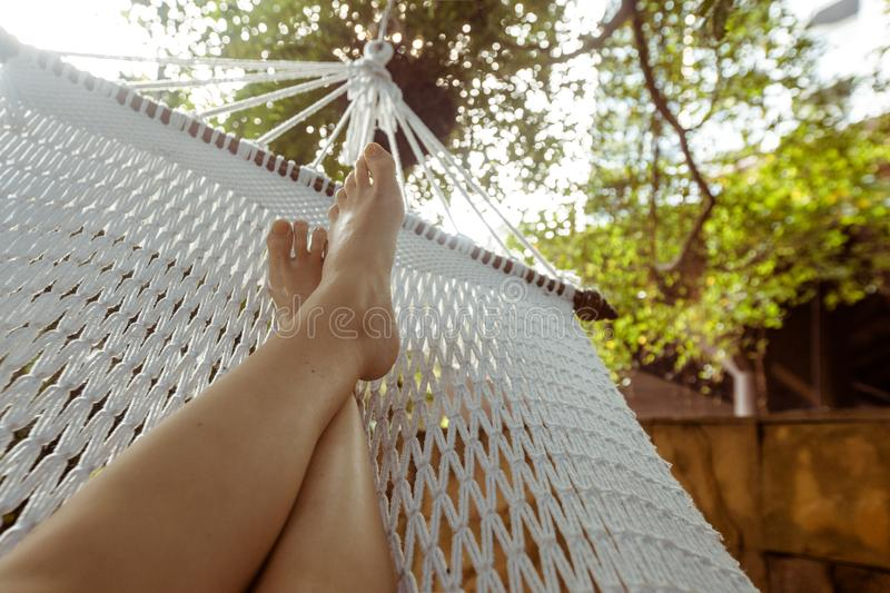 Crop person chilling in hammock. Crop shot of barefoot feet lying in white hammock and lounging in backyard royalty free stock photography