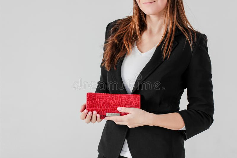 Crop photo of smiling women in black suit with red purse on gray stock photo