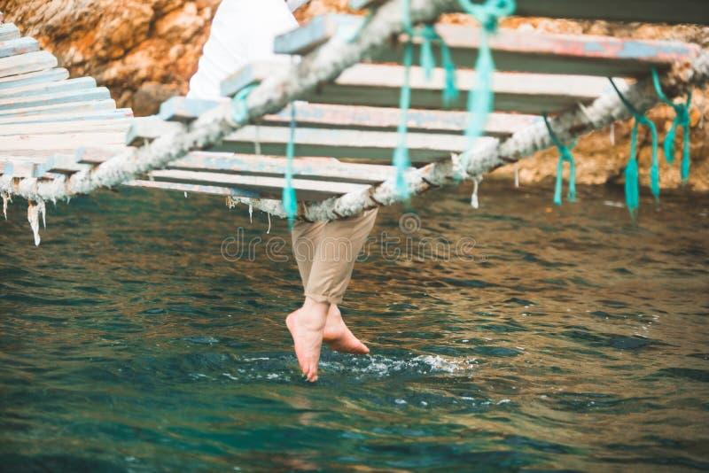 Crop picture man sitting at suspension bridge put legs in sea water royalty free stock photo